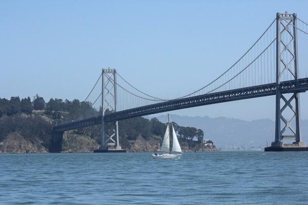 sailboat going under the bridge.